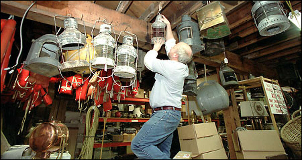 John Coulson, co-owner of Cuttysark, takes down a ship's light that will be on display at the nautical store's reopening Saturday. The 20-year-old Bellevue business was damaged in December when fire destroyed neighboring Masins Furniture. Cuttysark is brimming with unique marine items such as lanterns, cedar fishing floats, portholes and models of historic ships.