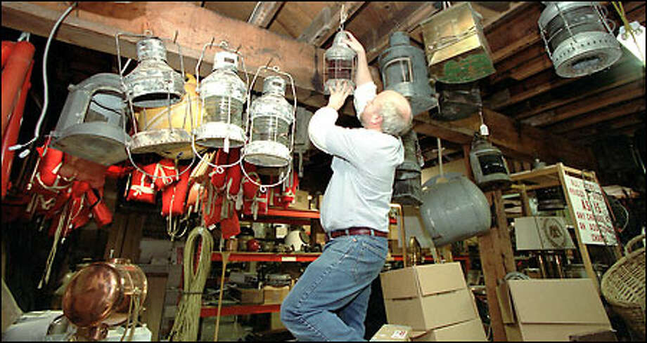 John Coulson, co-owner of Cuttysark, takes down a ship's light that will be on display at the nautical store's reopening Saturday. The 20-year-old Bellevue business was damaged in December when fire destroyed neighboring Masins Furniture. Cuttysark is brimming with unique marine items such as lanterns, cedar fishing floats, portholes and models of historic ships. Photo: Phil H. Webber, Seattle Post-Intelligencer / Seattle Post-Intelligencer