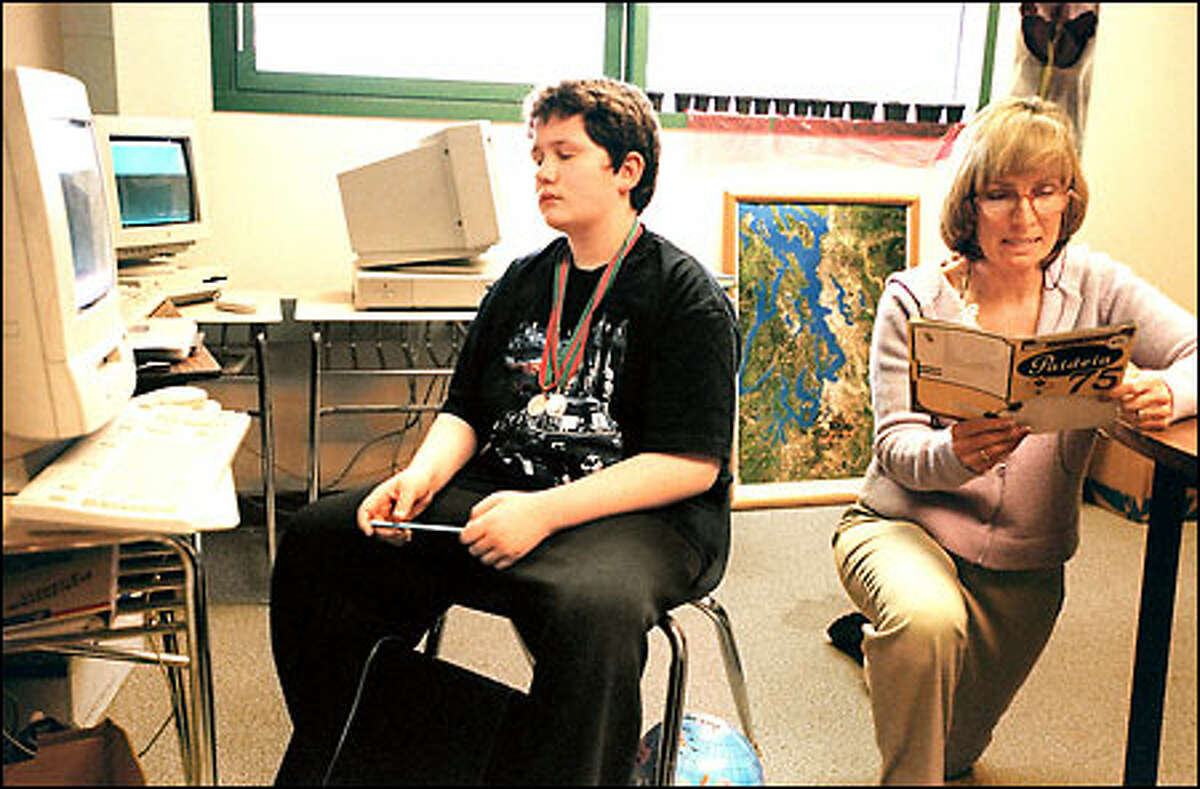Michael Inderkum practices spelling with teacher Margy Ordell. Michael has autism but has become one of the Mill Creek school's best spellers.