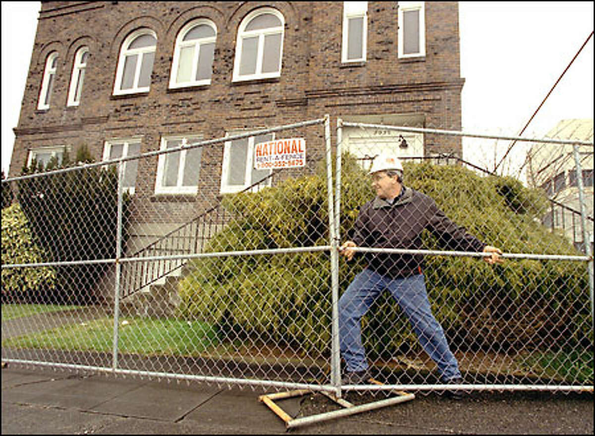 Don Daschuk, an employee of PCL Construction Co., secures a section of fence in front of the old Scottish Rite Temple in downtown Everett, where the new arena will be built.