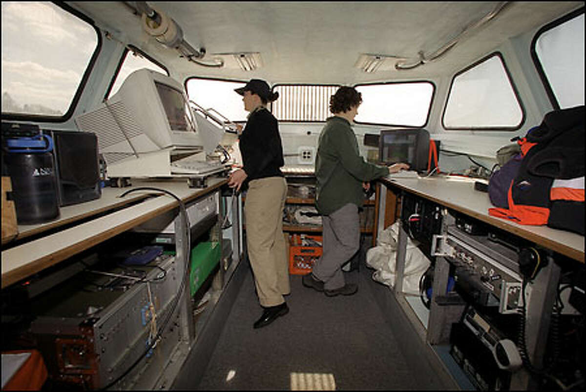 Navy Ensign Angie Messer, left, and Shyla Allen, a survey technician with NOAA, keep an eye on computer monitors in the bow of one of six boats used in a survey of Puget Sound's floor.