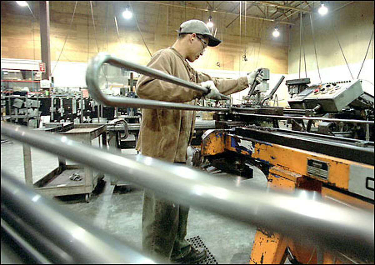 Qui Lam works on a bus bicycle rack at Sportworks in Woodinville. The order from Metro transformed the company from a contract manufacturer into a business with its own product.