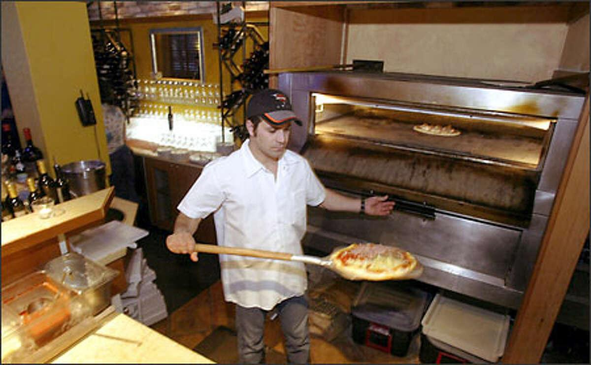 Pizza chef Agostino Trentacoste pulls a pie out of the oven at La Vita e Bella Pizzeria on Second Avenue. The pizzas are often served true Italian style: uncut.