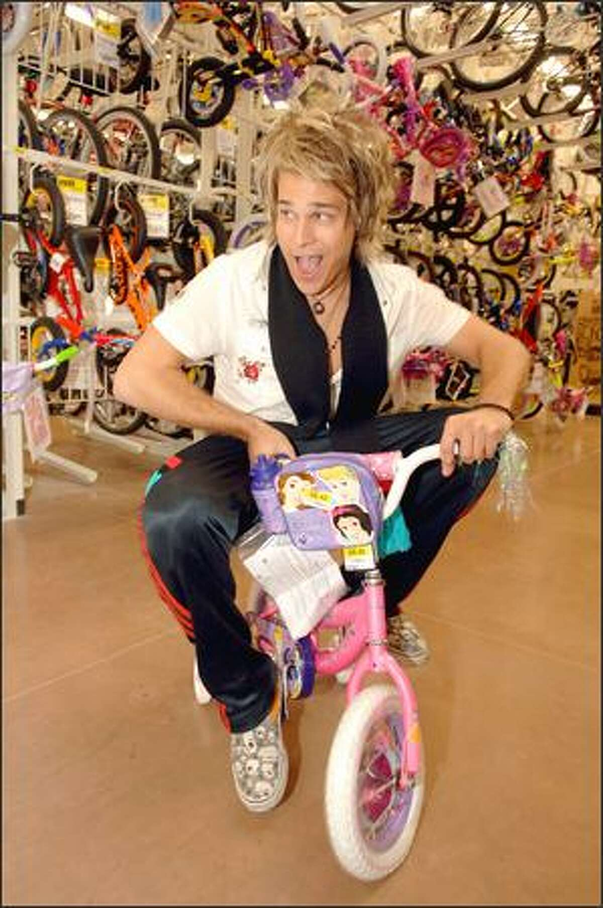 Attention Wal-Mart shoppers: Ryan Cabrera, a pop star of that not-quite-distinctive-but-resembling-Dave-Matthews-and-Goo-GooDolls quality, plays around before he goes on stage to entertain at a celebration of the discount giant's 2,000th Supercenter in California.