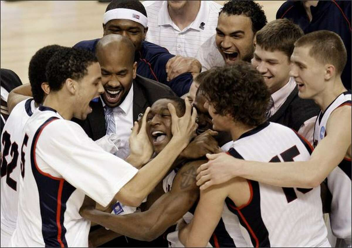 Gonzaga's Demetri Goodson, center, is hugged by teammates after scoring the winning shot against Western Kentucky during the second-round NCAA tournament game Saturday, March 21, 2009, in Portland, Ore. Gonzaga defeated Western Kentucky 83-81. (AP Photo/Rick Bowmer)