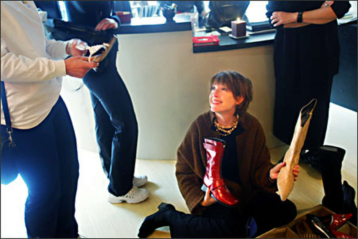 Mu.Shoe owner Susan Wilson talks with customers as she considers shoes for fall, brought to her by a Pazzo Footware rep.