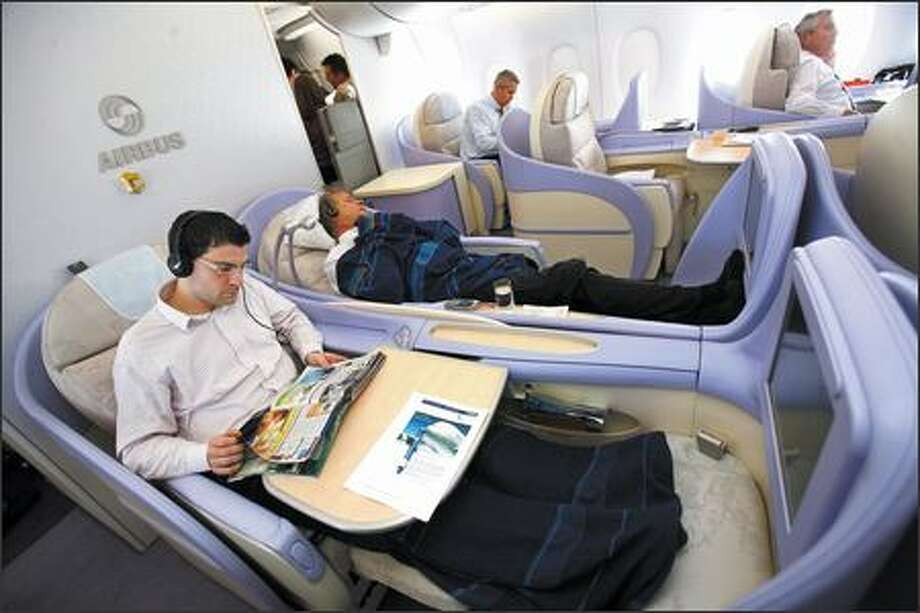 Passengers relax during travel from Frankfurt to New York in the Airbus A380, Monday. Airbus SAS's 555-seat, double-decker A380, the largest passenger plane ever built, made its U.S. debut today, with planes landing within 18 minutes of each other in New York and Los Angeles. Photo: Bloomberg News / Bloomberg News