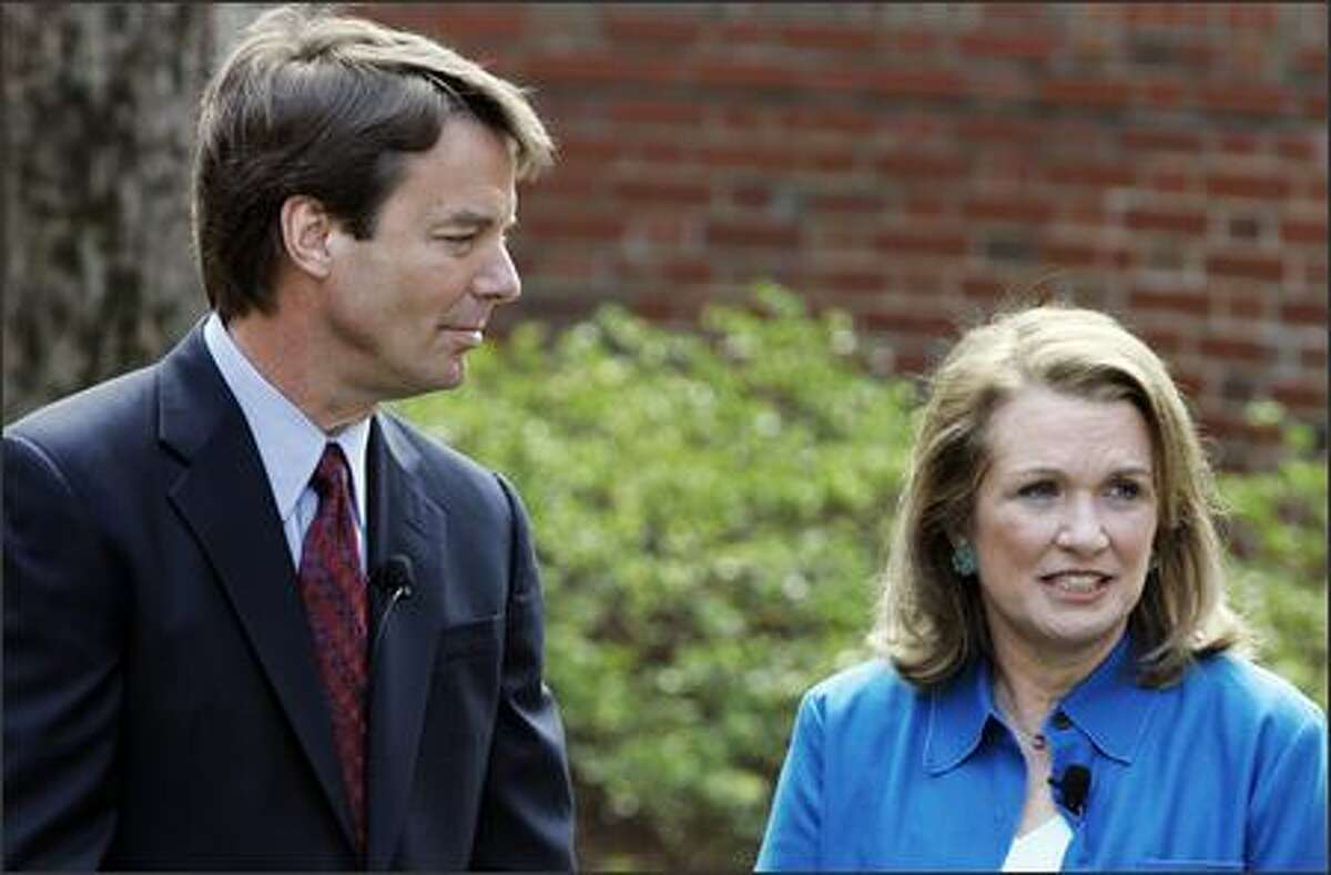 Democratic Presidential hopeful John Edwards, left, listens to his wife Elizabeth speak about her recurrence of cancer during a news conference in Chapel Hill, N.C., Thursday. Edwards will continue his campaign for the presidency. (AP Photo/Gerry Broome)
