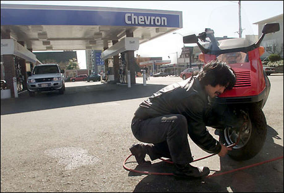 Will Tanaka fills a tire at a University District Chevron station near Sound Transit's planned rail line. Gasoline contaminates the groundwater here. Photo: Paul Kitagaki Jr., Seattle Post-Intelligencer / Seattle Post-Intelligencer
