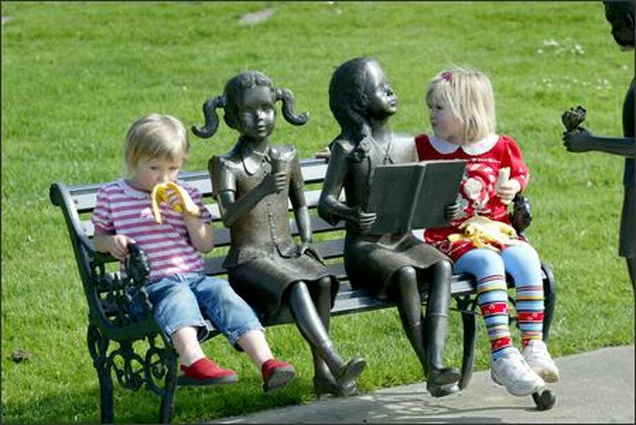 """Liana, 4, and Evelina Tereshchenko, 5, of Mill Creek eat lunch at Houghton Beach Park in Kirkland yesterday in the company of a sculpture titled """"First Romance."""" Photo: Scott Eklund, Seattle Post-Intelligencer / Seattle Post-Intelligencer"""