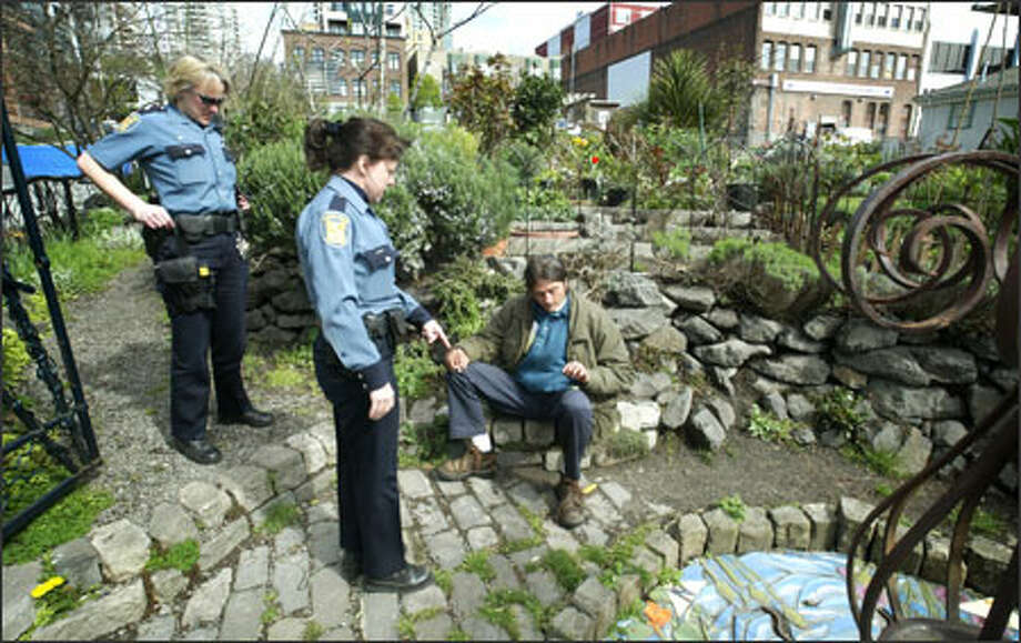 Seattle police officers question a man at the Belltown P-patch, which neighbors say is often abused by visitors. Volunteers have worked for many hours on the P-patch. Photo: Dan DeLong, Seattle Post-Intelligencer / Seattle Post-Intelligencer