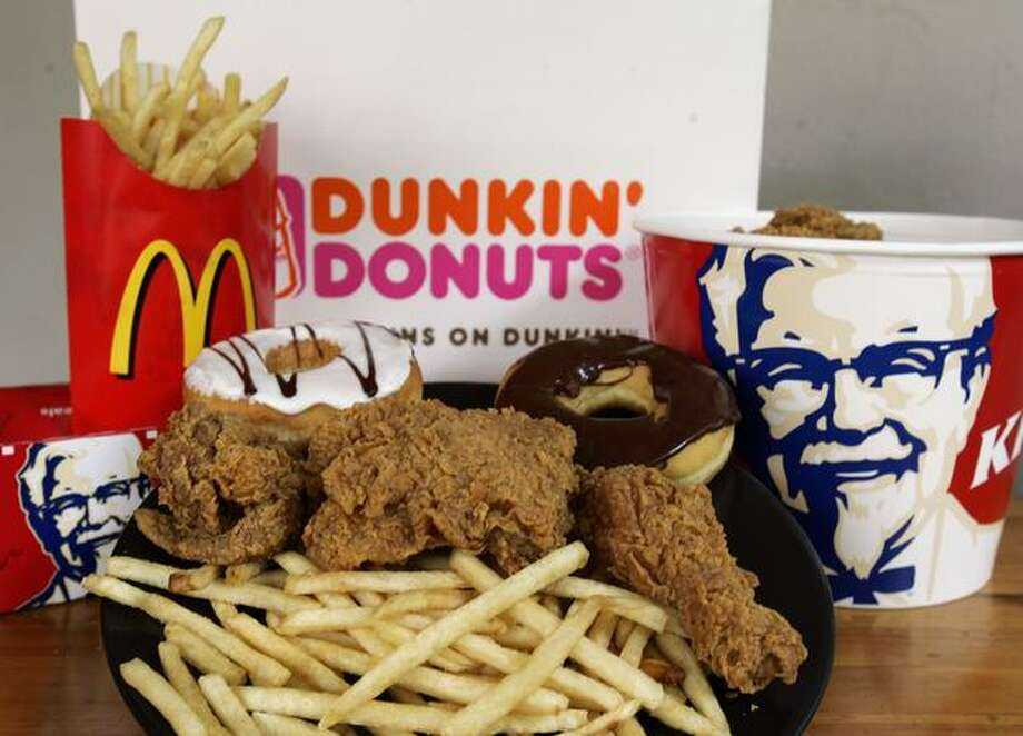 Doughnuts from Dunkin' Donuts, French fries from McDonalds and fried chicken from Kentucky Fried Chicken are displayed in this September 2006 file photo. Photo: Getty Images / Getty Images