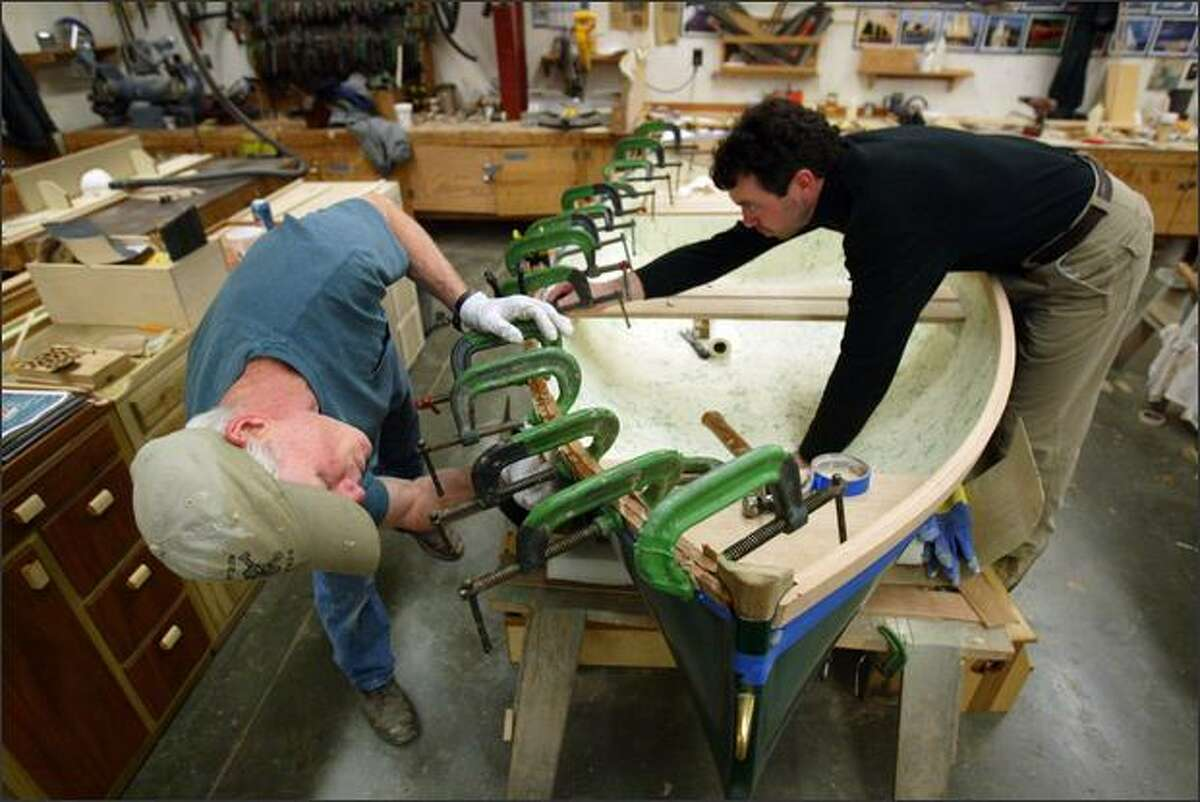 Marine carpentry students Frank Worsham, left, and Steve Guiling put the finishing trim on a boat during a class at Seattle Central Community College.