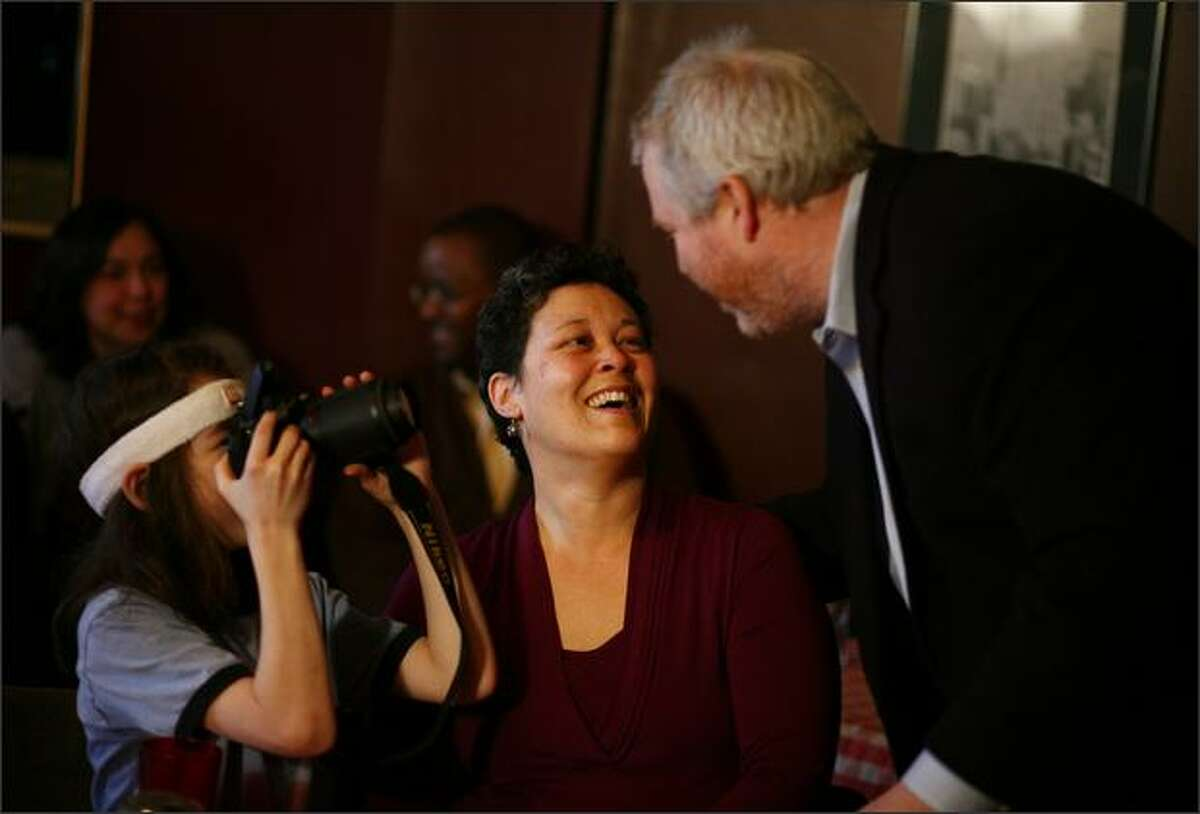 Michael McGinn, right, is photographed by his son Cian as he hugs his wife Peggy Lynch after announcing his candidacy for Mayor of Seattle on Tuesday at Piecora's Pizza in Capitol Hill.