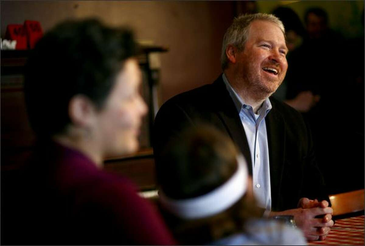 Michael McGinn announces his candidacy for Mayor of Seattle on Tuesday at Piecora's Pizza in Capitol Hill while seated next to his wife Peggy Lynch and son Cian McGinn, 9, foreground.