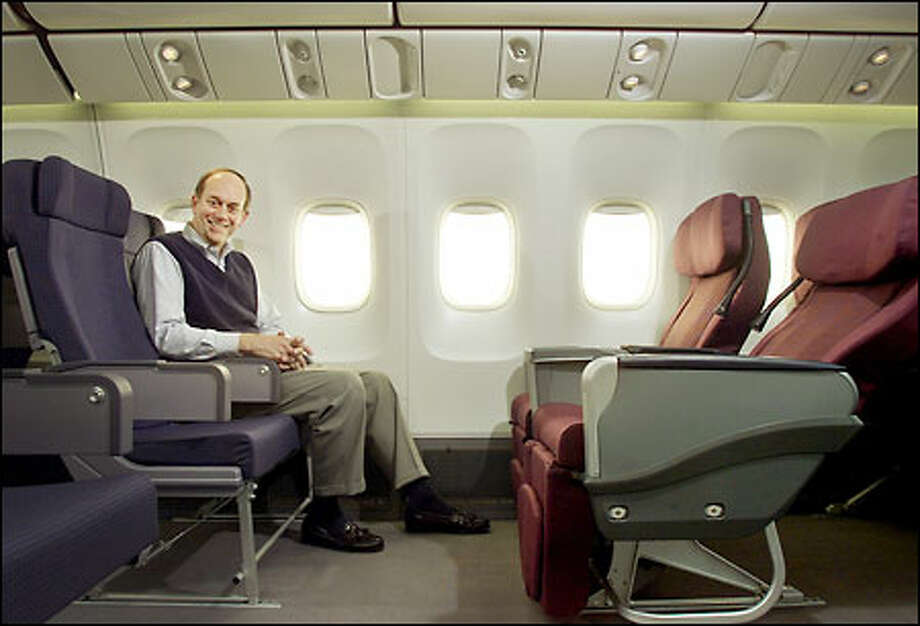 The Boeing Co.'s John Roundhill shows off the new 777-style interior in a mock-up of a 767 cabin at the commercial airplane headquarters in Longacres. Photo: Phil H. Webber, Seattle Post-Intelligencer / Seattle Post-Intelligencer