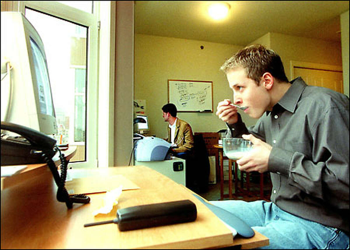 Lon McGowan eats breakfast while at work at his home/office, an apartment in Belltown. In the background is friend and company CFO John Schmitz. The two are moving the business into a Pioneer Square office.