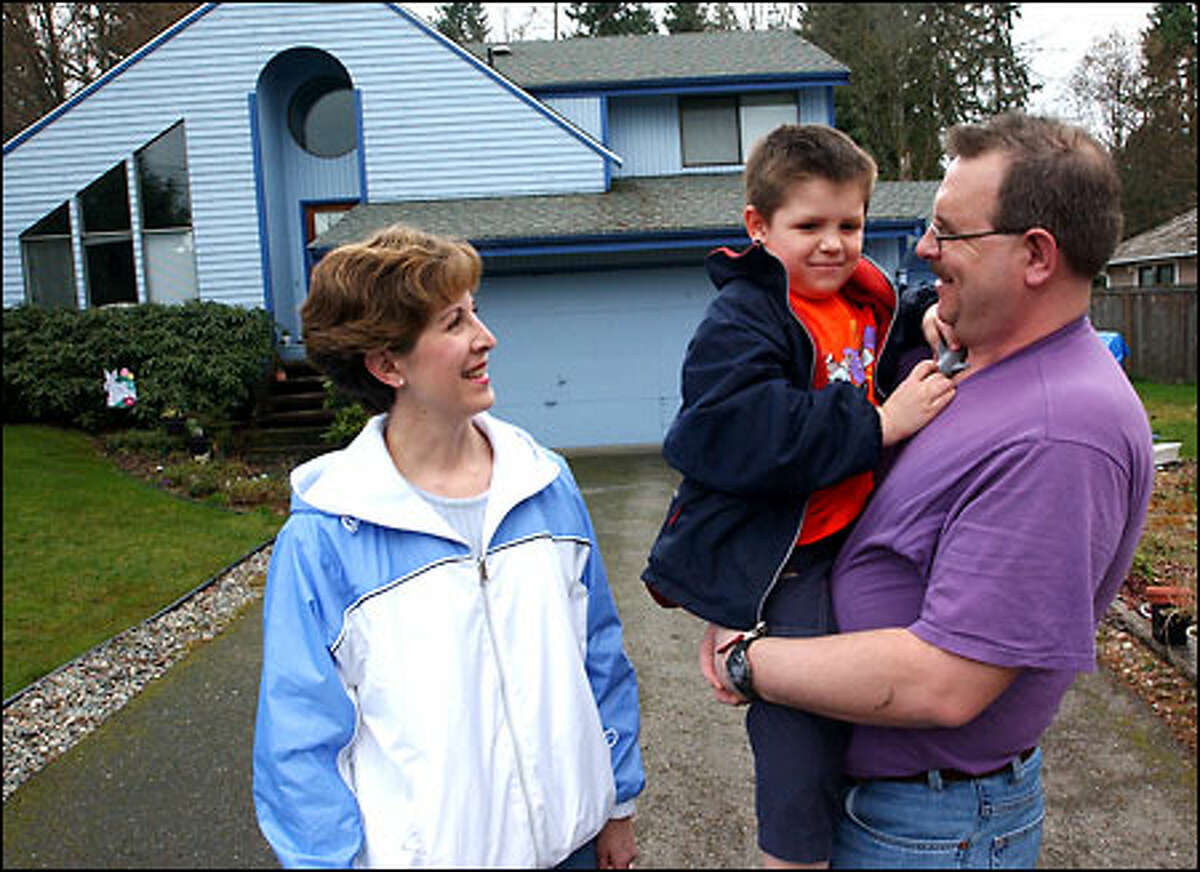 Eastmont resident Stephen Travis, at right with his 5-year-old son, talks with neighbor Jane Ann Pighin about their public services. Emergency fire calls now go to King County, even though a Bellevue fire station is minutes away.