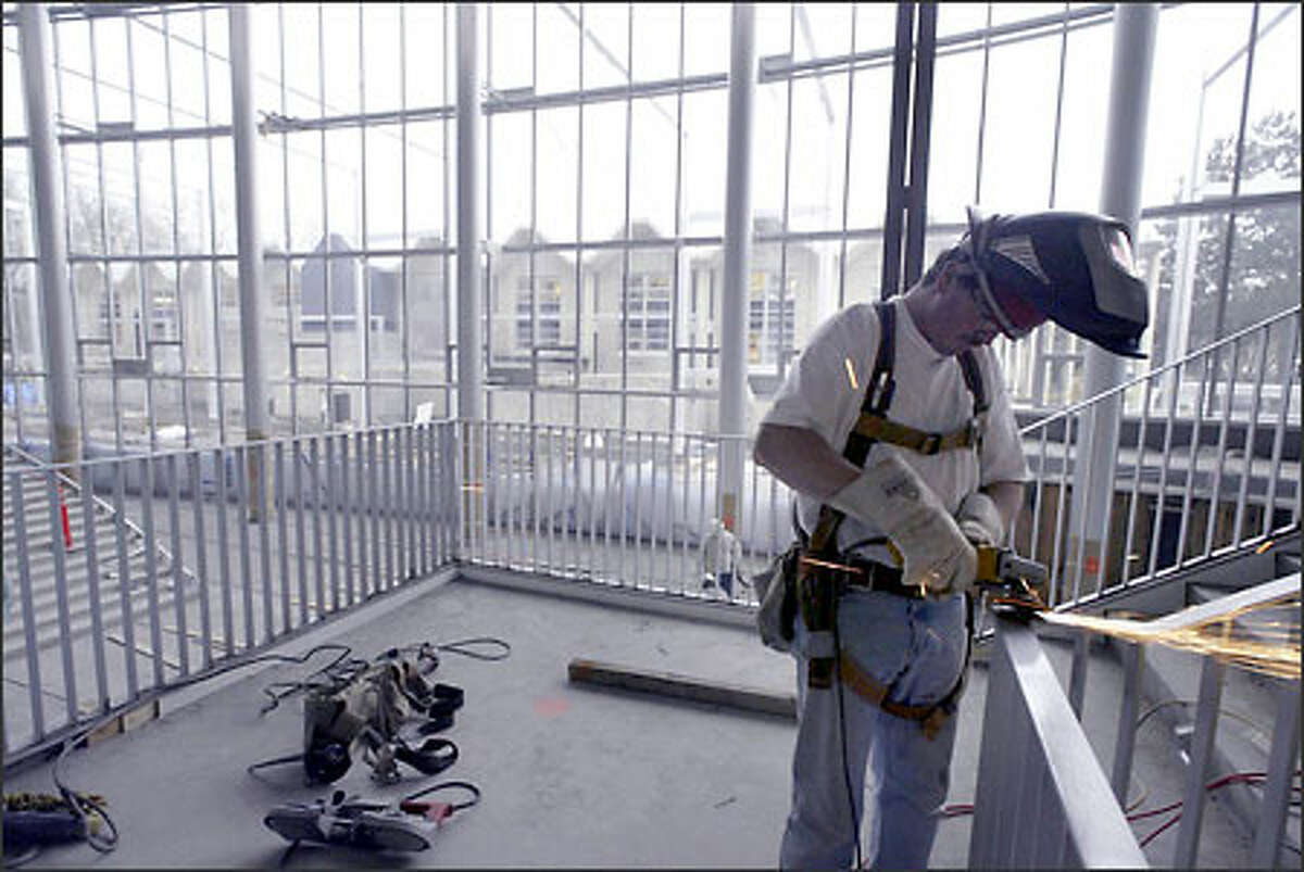Welder Bill Laidlaw grinds down a weld on the steel railing lining a stairway in McCaw Hall's grand five-story lobby. A massive, 220-foot-long bank of windows curves sinuously across the building's front, which faces the Phelps Center.