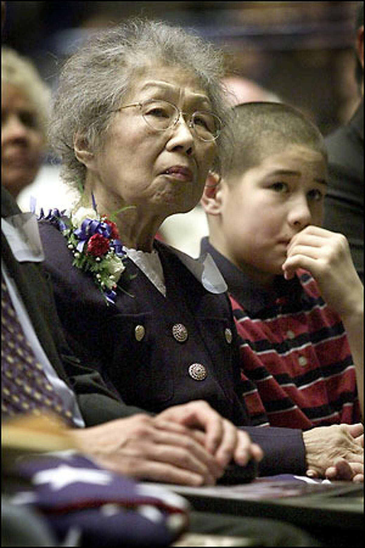 Hisakoi Funai, widow of Pfc. William Nakamura, listens with her grandson, Evan Spong, 13, as Eric Saul describes the heroics of her husband during World War II. Nakamura was awarded the Medal of Honor today at the Mercer Arena.