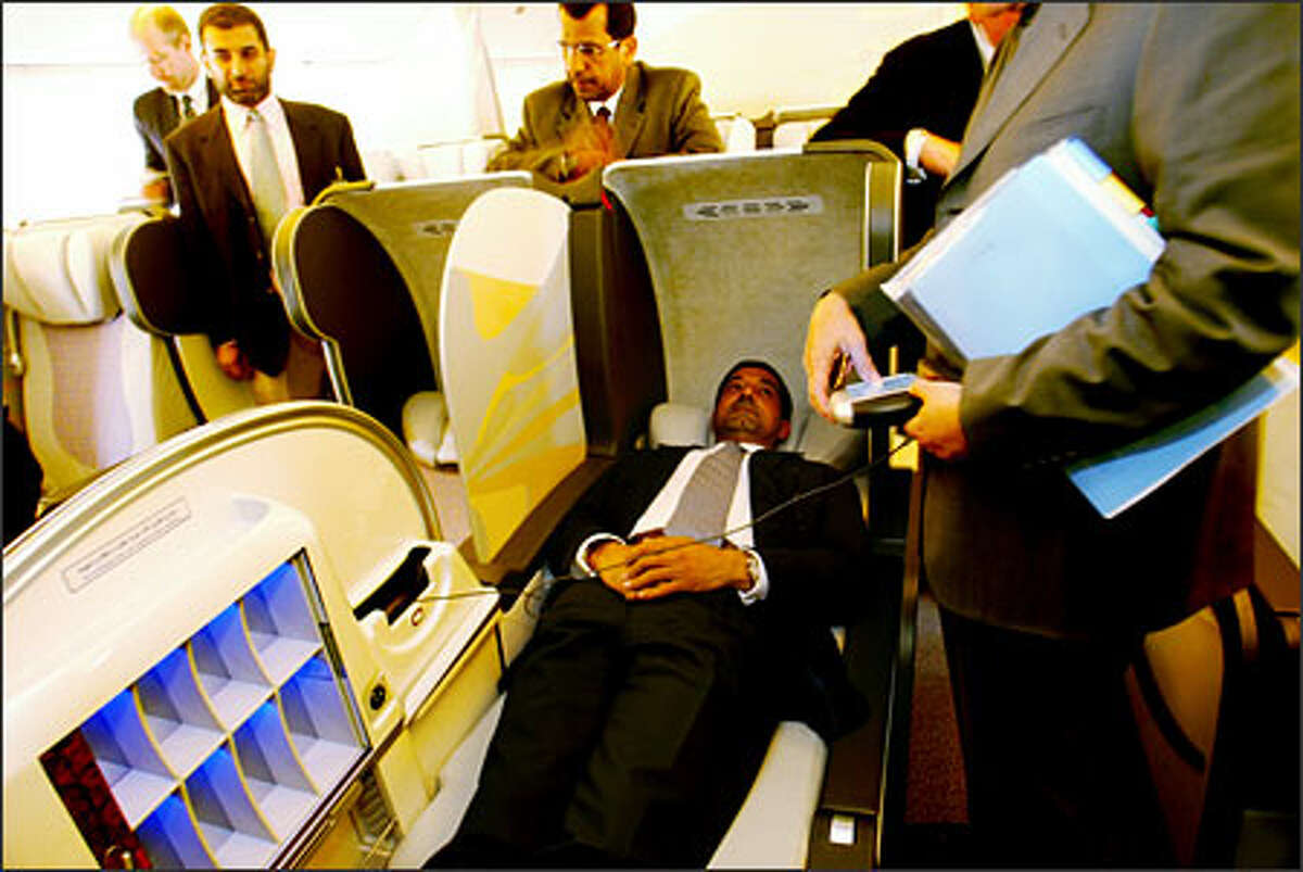 Sheikh Ahmed bin Saeed Al-Maktoum, Chairman of the Emirates Group, gets a demonstration of a first class reclining seat as he tours a new 777-300 ER purhcased by Emirates Airlines.