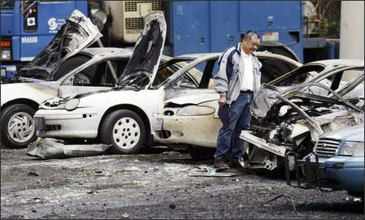 Curtis Ko, vehicle maintenance manager for the City of Seattle Fleets and Facilities Department, investigates the burn wreckage of several city fleet cars Monday. Twelve city vehicles were deliberately set on fire early Monday morning in a city parking lot at Airport Way and S. Royal Brougham Avenue.