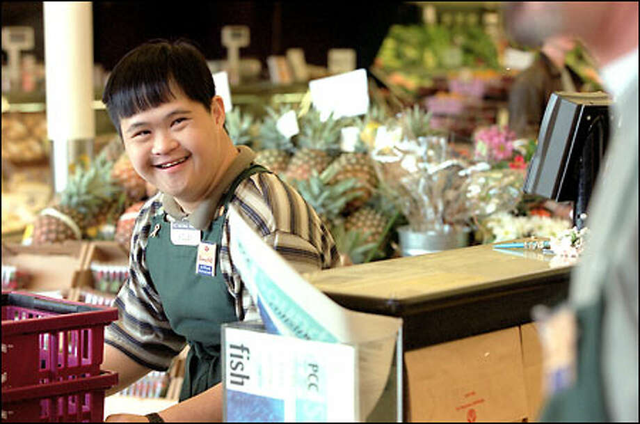 Adley Guanlao, a courtesy clerk at the PCC Natural Market in West Seattle, always has a smile for customers. Guanlao has Down syndrome. Photo: Phil H. Webber, Seattle Post-Intelligencer / Seattle Post-Intelligencer