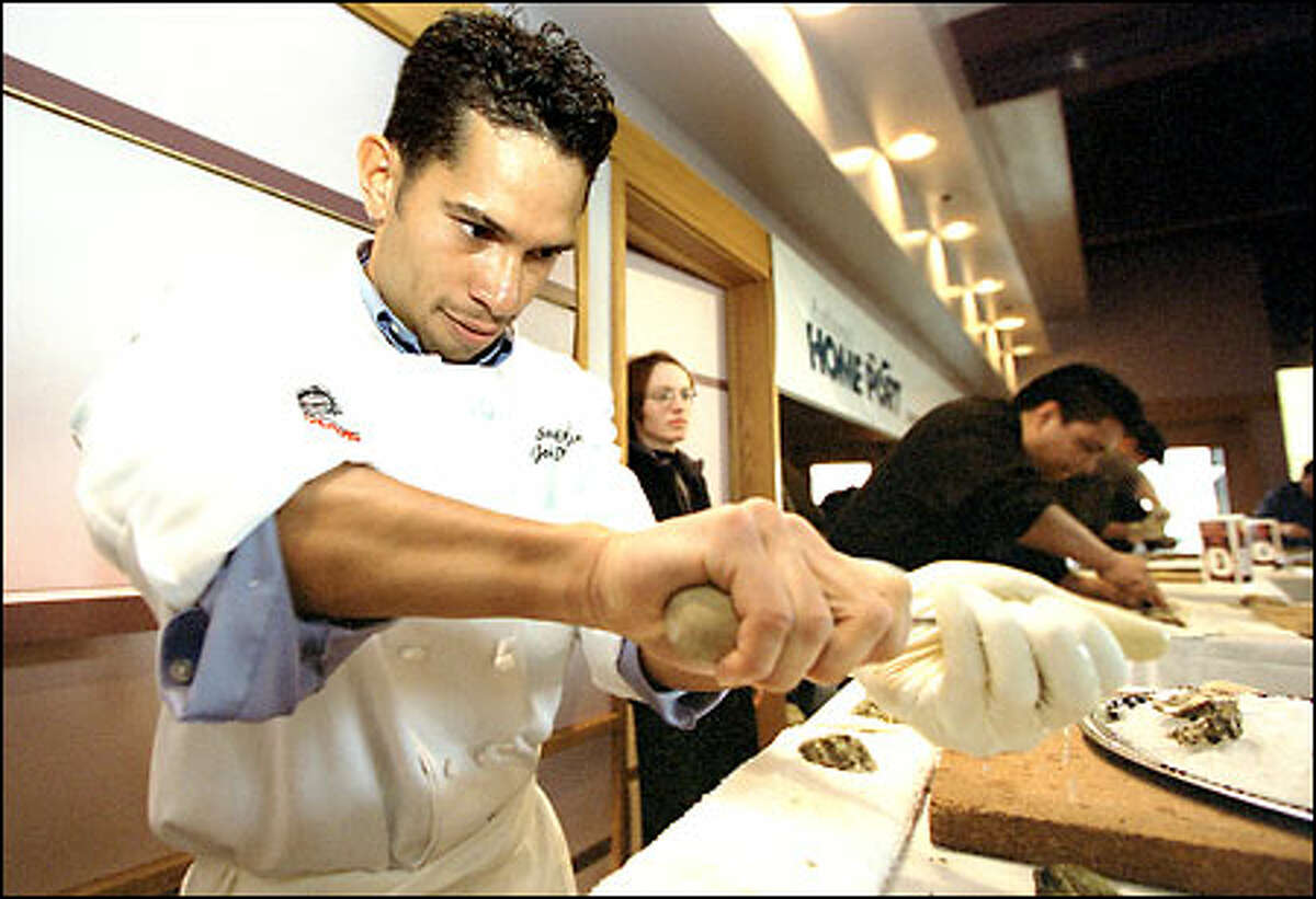 John Duran, a chef at Chinook's at Salmon Bay, works feverishly to open Kumamoto oysters during an oyster-shucking contest.