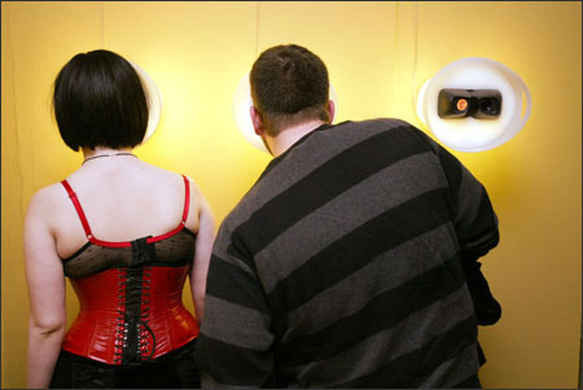 Mary Rose Hagstrom and Todd Mace check out the peep-show art at the Seattle Erotic Art Festival at Consolidated Works. This display is essentially View-Master for adults.