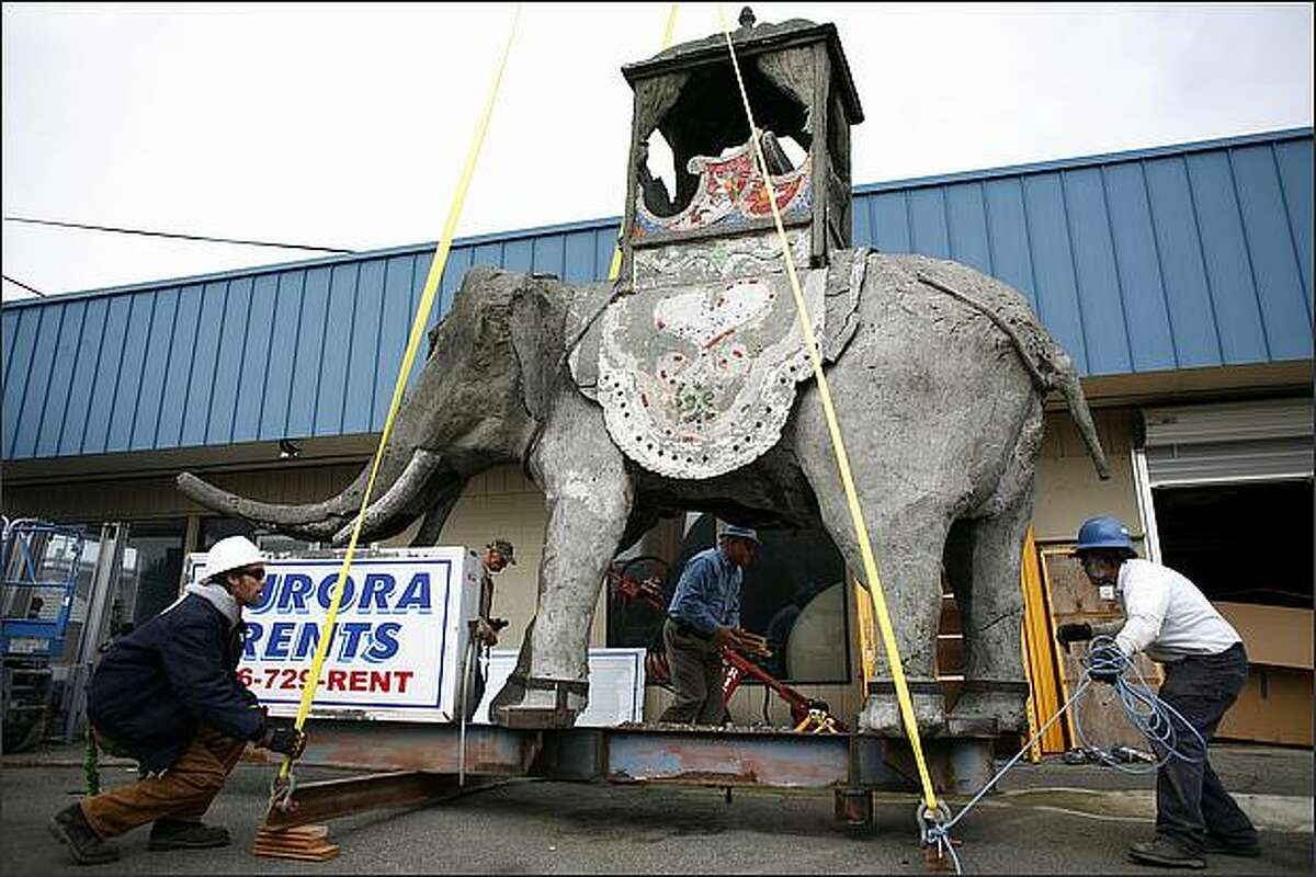 Chris Beasley,left, and Scott Laabs, right, with Shoreline Sign and Awning, lower an 8,400 pound concrete elephant in front of Aurora Rents in north Seattle on March 26, 2009. The elephant, built in the 1920s and sitting high above Aurora Avenue North since 1946, was removed for restoration.