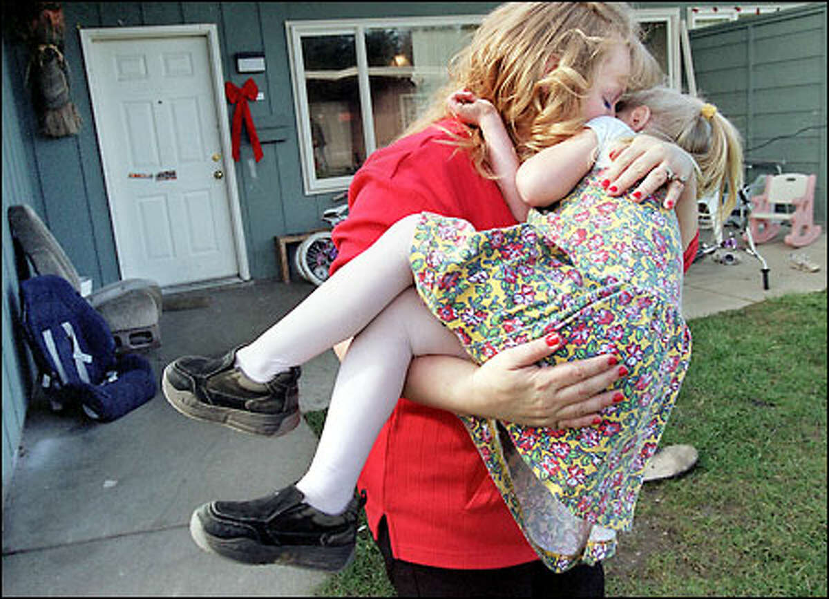 Melody Dady snuggles with her 4-year-old daughter Suzanne at their home in Port Angeles where Melody lives with her husband, Michael, and three children. Suzanne was just a baby when welfare workers took away Melody's children. She got them back after kicking her methamphetamine habit at the third attempt.