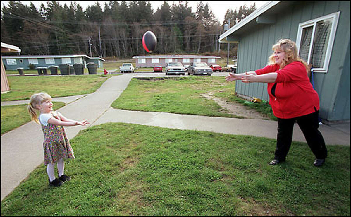 Melody Dady, right, plays catch with her daughter Suzanne, 4, at their home at Mt. Angeles View Public housing project in Port Angeles.