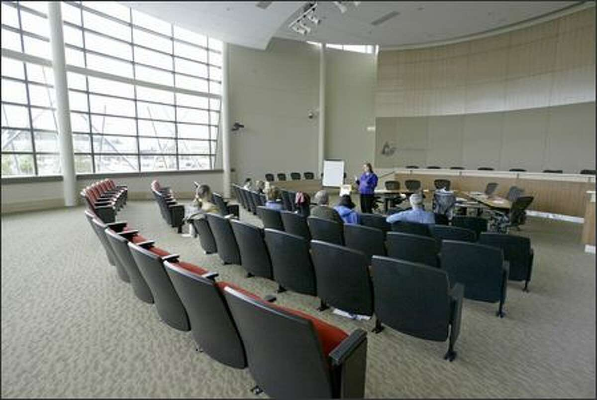 A local group holds a meeting in Redmond City Hall's council chamber. Most of the chamber's east wall is glass. The transparency of the new City Hall is an obvious symbol for open government.
