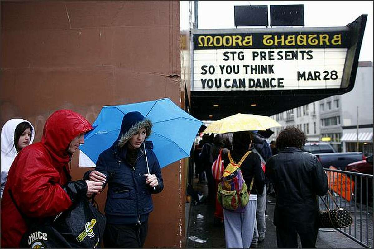 People wait in the rain on Saturday morning outside the Moore Theater in Belltown. A line stretched around the block as people waited for their chance to perform for the television show