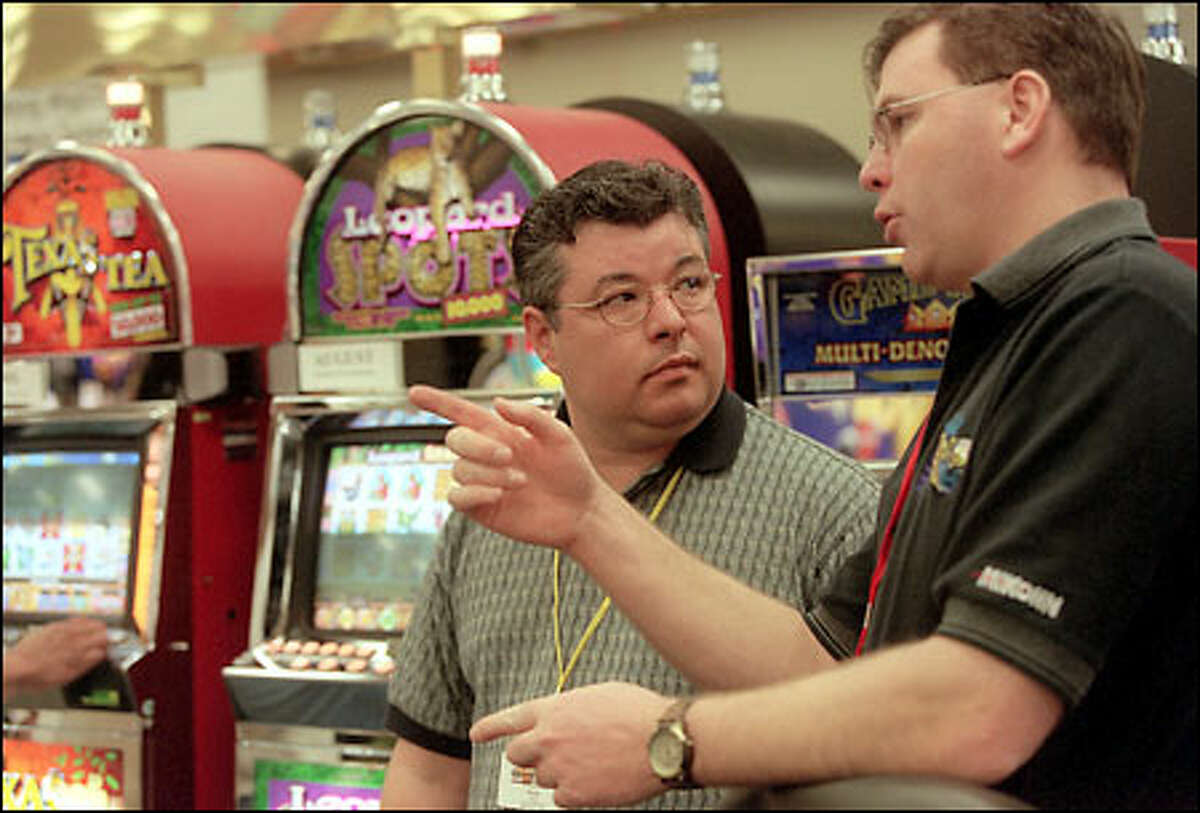 Doug Boon, left, of the Nisqually Red Wind Casino talks with Tom Hardy of gambling supplier Mikohn Products at a trade show yesterday in Anacortes.