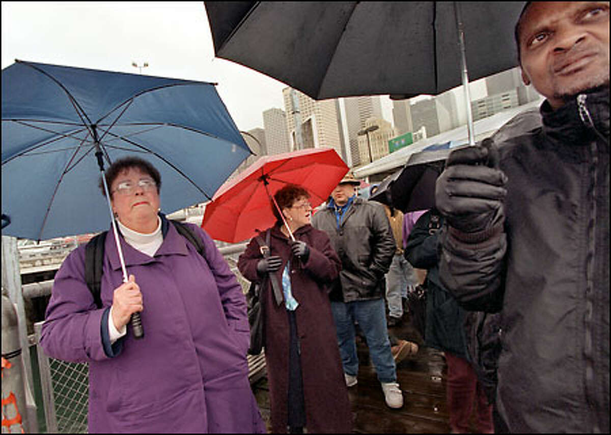 """Not happy about proposed higher fares for the state's ferries, commuters Mary Collier, left, Lena Swanson and Jerry Lynch, right, wait for an afternoon ferry from Seattle to Bremerton yesterday. """"It's not right. Some people just can't afford it,"""" Lynch said. """"It's too big of an increase at once,"""" Collier said."""