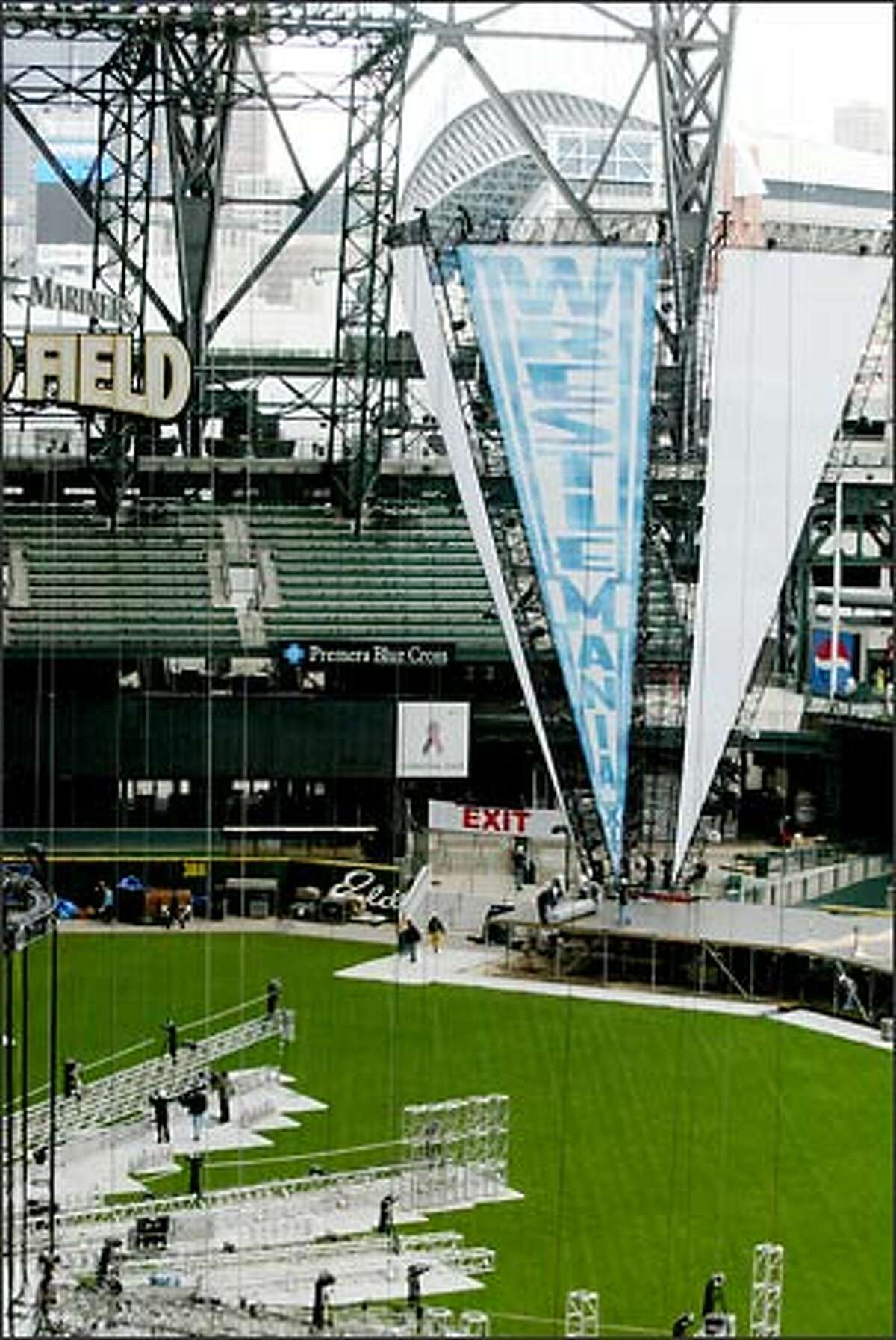Workmen set up the WrestleMania XIX at Safeco Field. It takes 14 trucks to carry all the gear. The primary WWE road crew is responsible for 104 television shows and 12 pay-per-view events each year.