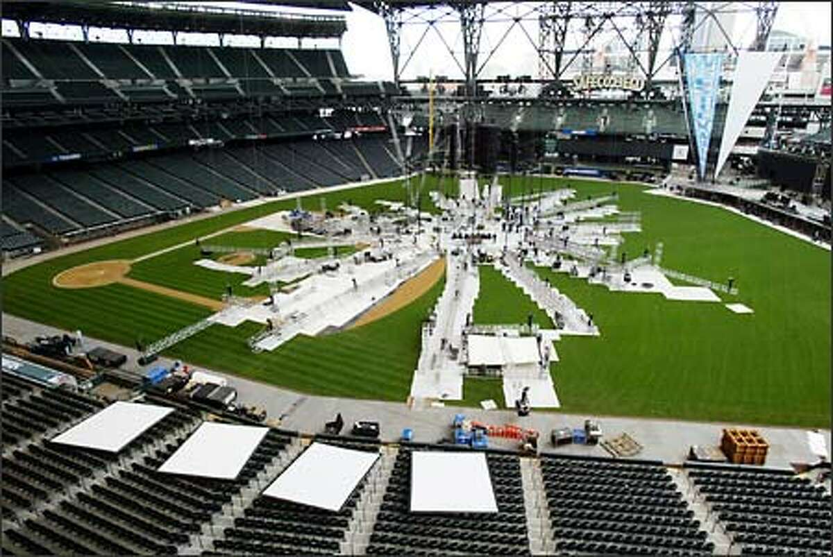 Workmen install the ring, stage and lighting for the WrestleMania at Safeco Field. Semi-rigid panels cover and protect the grass during setup. Other patches of the field are left exposed to the sun to keep the grass healthy.