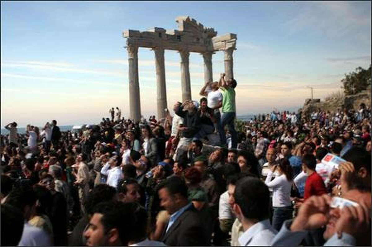 Astronomy enthusiasts and tourists gather around the Apollo Temple to view a solar eclipse in the Turkish Mediterranean coastal resort of Side, Antalya, Wednesday March 29, 2006. The total solar eclipse began at sunrise on the eastern tip of Brazil, crossed the Atlantic and maked landfall in Ghana, headed north across the Sahara, the eastern Mediterranean, Turkey and the Black Sea, and on into Central Asia, where it will finally die out at sunset in Mongolia.(AP Photo/Burhan Ozbilici)