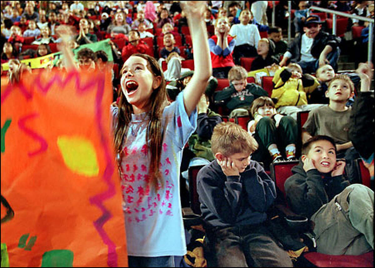 Claire Elizabeth Carey, 9, responds to a big TV screen at the Seattle Sonics' 'Read to Succeed Jam' yesterday at KeyArena while her classmates Stephen Rasmussen, 9, center, and Rodney Rabanal, 8, right, from B.F. Day School in Fremont, have a different reaction.