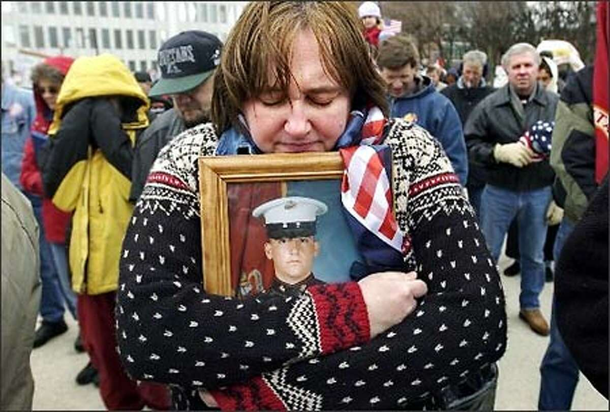 Nancy Rodriguez of Rockford, Mich., holds tight a framed photo of her son, Joshua Rodriguez, 21, who is currently deployed in Iraq, as she bows her head in prayer during a troop support rally in Grand Rapids, Mich.