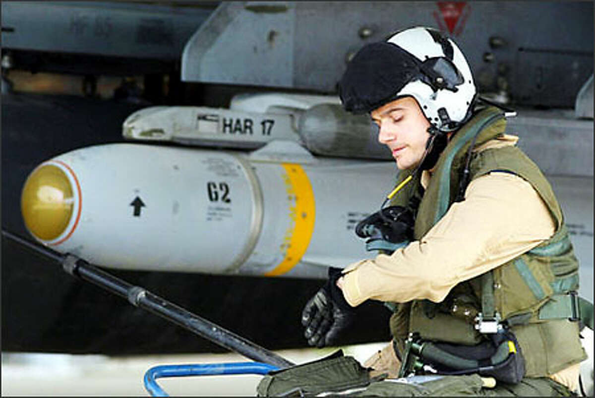 British pilot Flt. Lt. Paul Francis checks his watch as he sits beside the wing of his Harrier GR7, armed with a Maverick missile, at a base in Kuwait. U.S. Central Command said on Saturday there would be no