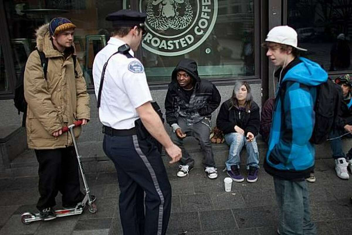 A private security officer asks Sam Liddell and Naima Nazovari, sitting on the sidewalk in front of a Starbucks coffee shop, to stand up because they are violating Seattle's sit/lie ordinance.