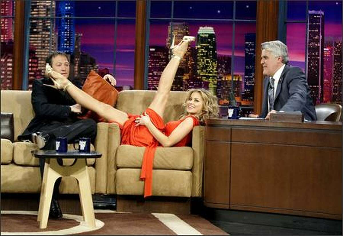 """Who needs to pay for a lap dance if you can get Carmen Electra to guest star on your talk show? Electra showed off her workout moves (and her legs!) Wednesday night to fellow guest star Rob Schneider and """"Tonight Show"""" host Jay Leno, who both seem speechless at the sight of Electra's superior flexibility."""