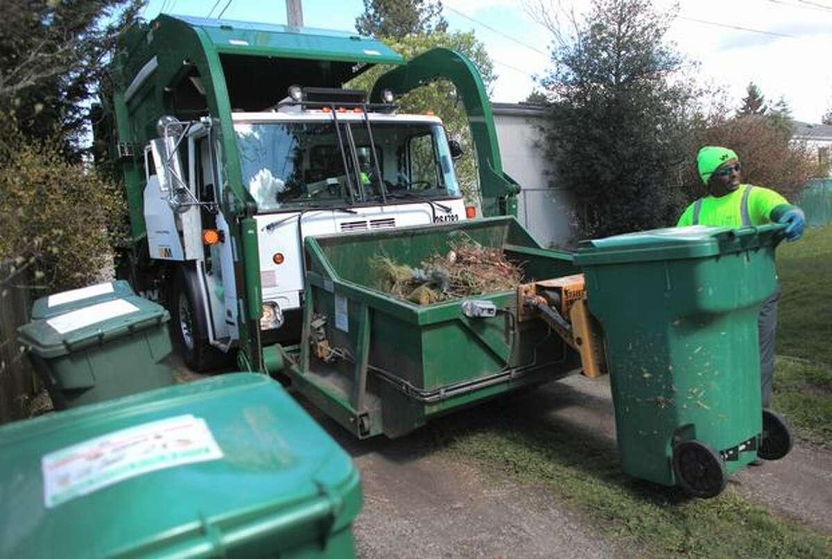 Eric Jones of Waste Management empties yard waste containers on Wednesday in Seattle's Greenwood neighborhood.