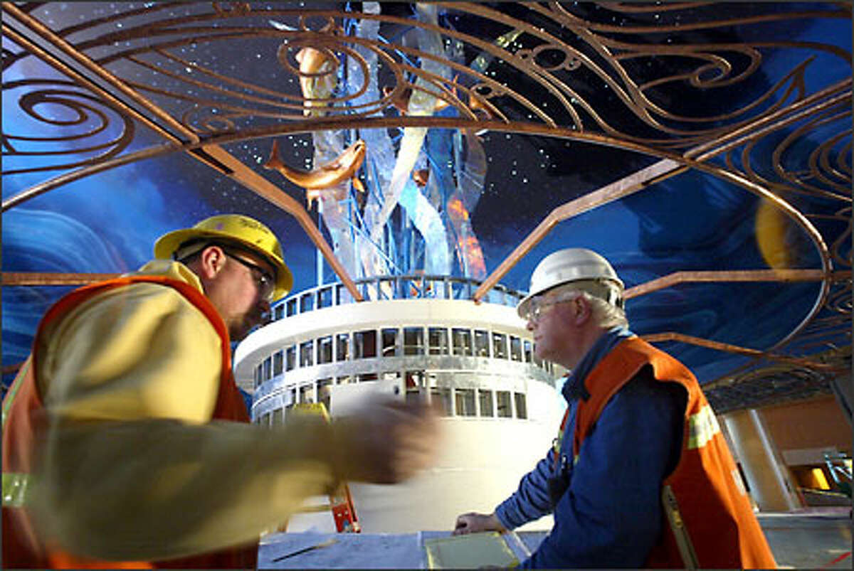 Brad Hansen of Sequoyah Electric and Dwain Rawley examine construction plans in front of a sculpture at the new Tulalip Casino north of Marysville.