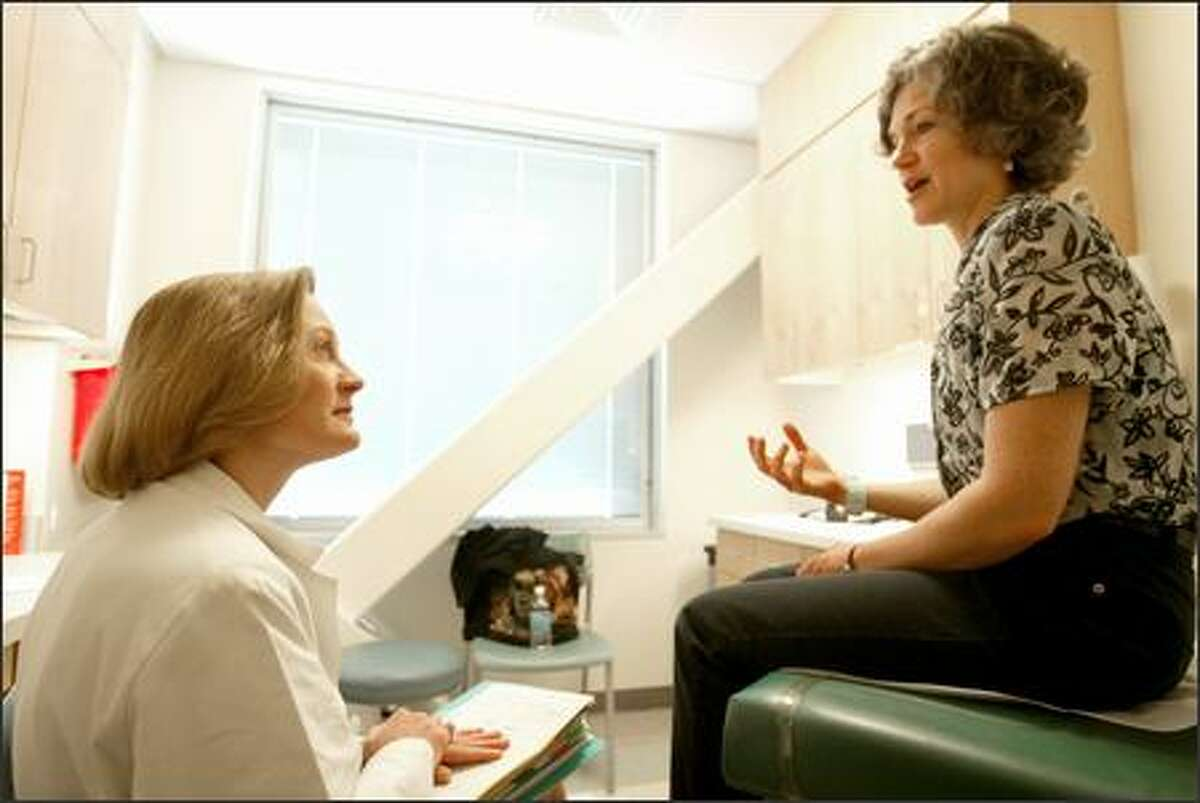 Dr. Julie Gralow, left, talks with cancer patient Starr Humphreys at her oncology clinic in Seattle. Gralow found that acupuncture has worked for Humphreys.