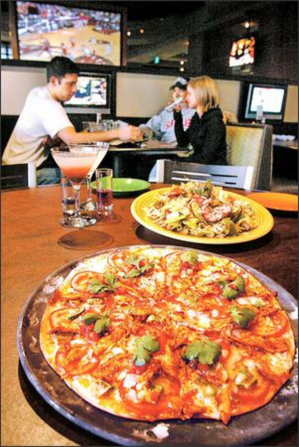 Spicy chicken on thin-crusted pizza and a colorful char siu chicken salad, rear, will grab your attention at Sport Restaurant.