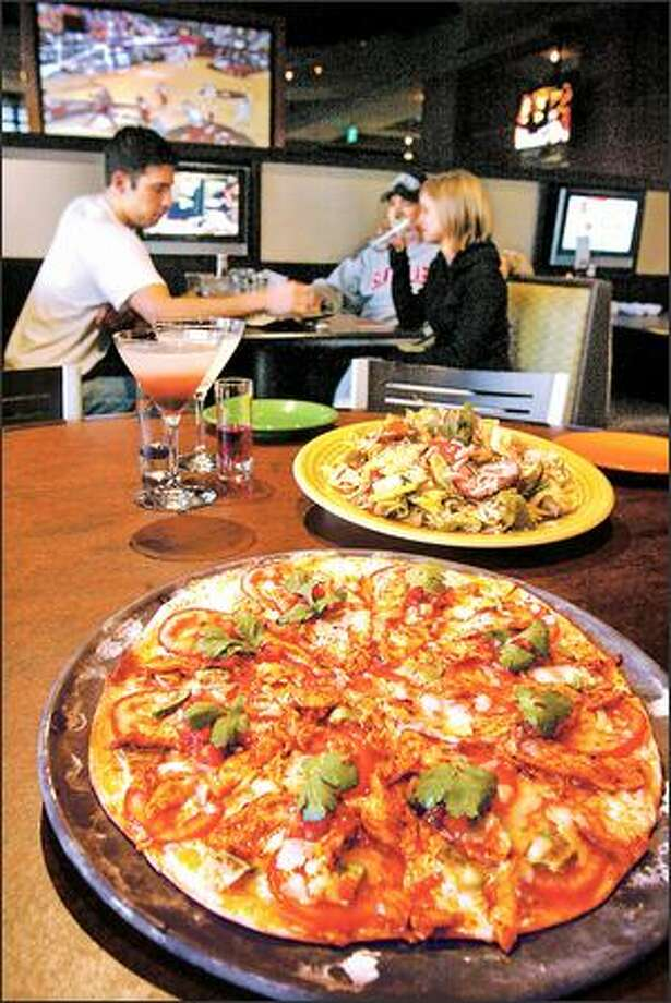 Spicy chicken on thin-crusted pizza and a colorful char siu chicken salad, rear, will grab your attention at Sport Restaurant. Photo: Paul Joseph Brown, Seattle Post-Intelligencer / Seattle Post-Intelligencer