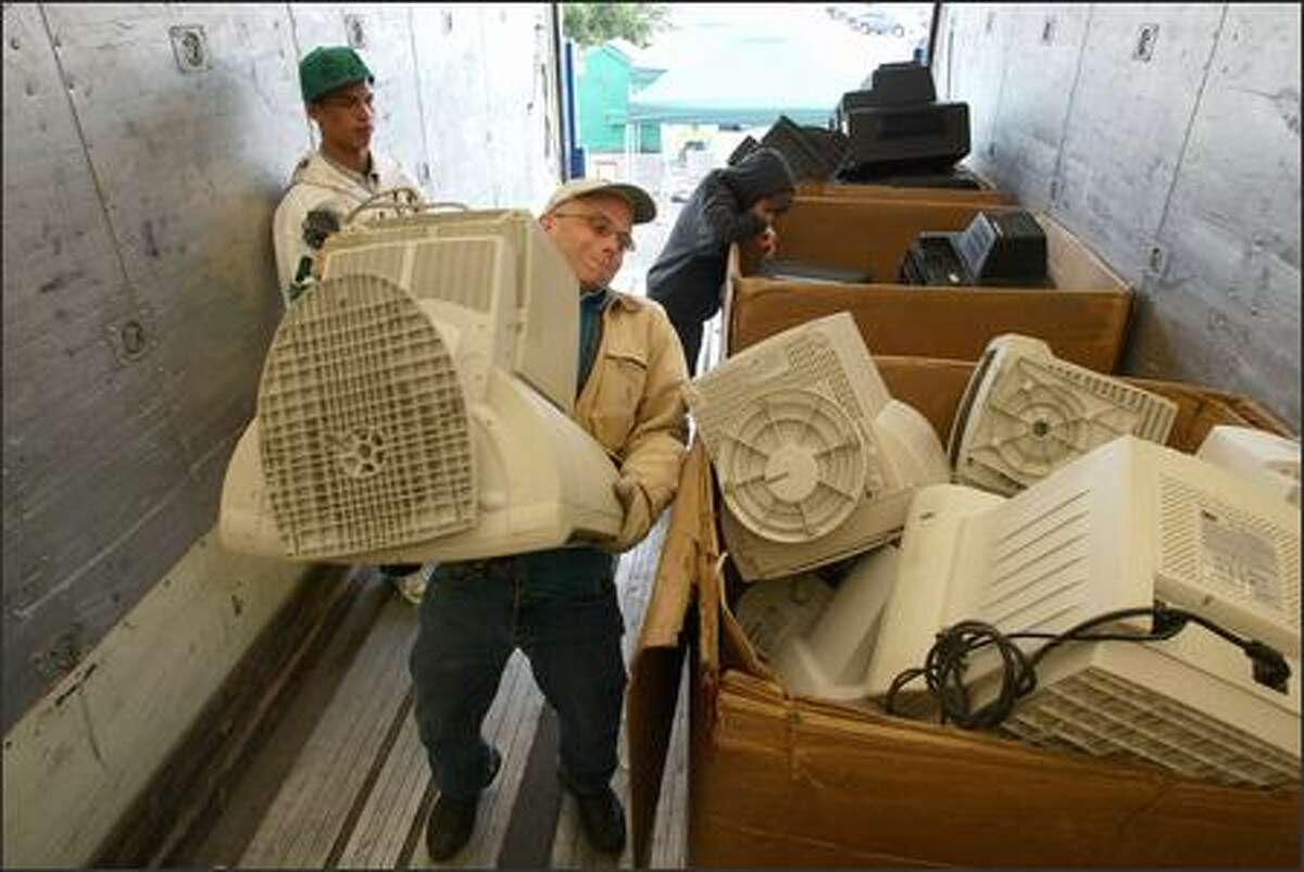 Paul Wagner heaves a mid-'90s Apple monitor into a bin during a daylong electronics recycling drive operated by EarthCorps and InterConnection at Magnuson Park on Sunday. Wagner works for InterConnection, a non-profit that provides refurbished computers to underserved communities locally and abroad. At left is Max Keeler, a 16-year-old volunteer from Seattle Academy.